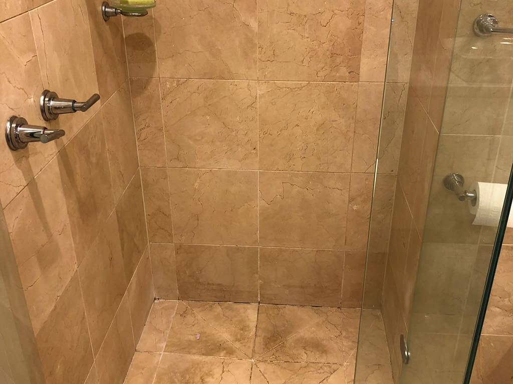 before shower restoration on a marble shower with mouldy grout and dirty tiles